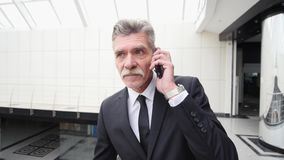 Επιχειρηματίας που μιλά στο τηλέφωνο στην οικοδόμηση του διαδρόμου Στοκ Εικόνες