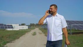 Επιχειρηματίας που μιλά στο τηλέφωνο στο υπόβαθρο των ηλιακών πλαισίων απόθεμα βίντεο