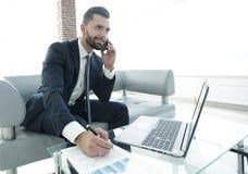Επιχειρηματίας που μιλά στο smartphone για τα οικονομικά έγγραφα Στοκ Εικόνα