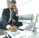 Επιχειρηματίας που μιλά στο smartphone για τα οικονομικά έγγραφα Στοκ εικόνες με δικαίωμα ελεύθερης χρήσης