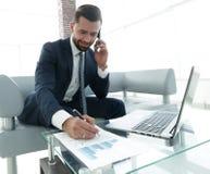 Επιχειρηματίας που μιλά στο smartphone για τα οικονομικά έγγραφα Στοκ Φωτογραφία