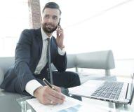 Επιχειρηματίας που μιλά στο smartphone για τα οικονομικά έγγραφα Στοκ φωτογραφία με δικαίωμα ελεύθερης χρήσης
