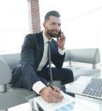Επιχειρηματίας που μιλά στο smartphone για τα οικονομικά έγγραφα Στοκ Εικόνες
