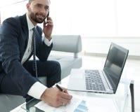 Επιχειρηματίας που μιλά στο smartphone για τα οικονομικά διαγράμματα Στοκ Εικόνες