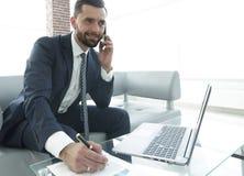 Επιχειρηματίας που μιλά στο smartphone για τα οικονομικά διαγράμματα Στοκ φωτογραφίες με δικαίωμα ελεύθερης χρήσης