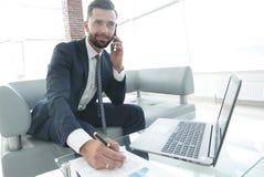 Επιχειρηματίας που μιλά στο smartphone για τα οικονομικά διαγράμματα Στοκ εικόνες με δικαίωμα ελεύθερης χρήσης