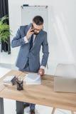 Επιχειρηματίας που μιλά στο smartphone εξετάζοντας τα έγγραφα στον εργασιακό χώρο Στοκ φωτογραφία με δικαίωμα ελεύθερης χρήσης