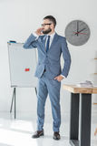Επιχειρηματίας που μιλά στο smartphone στεμένος στον εργασιακό χώρο στην αρχή Στοκ Εικόνα