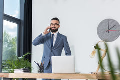 Επιχειρηματίας που μιλά στο smartphone στον εργασιακό χώρο με το lap-top στην αρχή Στοκ Εικόνες