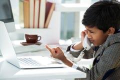 Επιχειρηματίας που μιλά μέσω του τηλεφώνου δείχνοντας στο lap-top στο γραφείο Στοκ Εικόνες