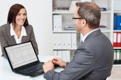 Επιχειρηματίας που μιλά σε έναν συνάδελφο στο γραφείο Στοκ εικόνα με δικαίωμα ελεύθερης χρήσης