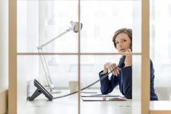 Επιχειρηματίας που μιλά σε ένα τηλέφωνο στο γραφείο Στοκ εικόνα με δικαίωμα ελεύθερης χρήσης
