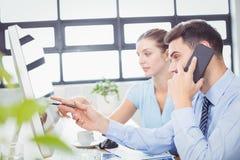 Επιχειρηματίας που μιλά στο κινητό τηλέφωνο δείχνοντας στο όργανο ελέγχου υπολογιστών Στοκ Εικόνα