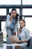 Επιχειρηματίας που μιλά στο κινητό τηλέφωνο ενώ συνάδελφος που χρησιμοποιεί ένα lap-top Στοκ εικόνα με δικαίωμα ελεύθερης χρήσης