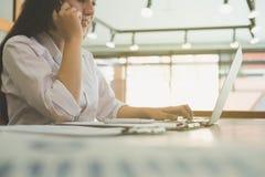 Επιχειρηματίας που μιλά στο κινητό τηλέφωνο εργαζόμενη στο lap-top ομο Στοκ Εικόνες