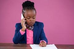 Επιχειρηματίας που μιλά στο κινητό τηλέφωνο διαβάζοντας τα έγγραφα Στοκ Εικόνες