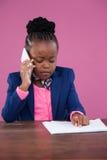 Επιχειρηματίας που μιλά στο κινητό τηλέφωνο διαβάζοντας την έκθεση Στοκ φωτογραφία με δικαίωμα ελεύθερης χρήσης