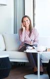 Επιχειρηματίας που μιλά στο κινητό τηλέφωνο και που γράφει στο διοργανωτή Στοκ Εικόνες
