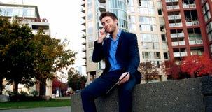 Επιχειρηματίας που μιλά στο κινητό τηλέφωνο και που κρατά την ψηφιακή ταμπλέτα απόθεμα βίντεο