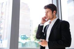 Επιχειρηματίας που μιλά στο κινητό τηλέφωνο κοντά στο παράθυρο στην αρχή Στοκ φωτογραφία με δικαίωμα ελεύθερης χρήσης