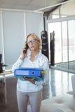 Επιχειρηματίας που μιλά στο κινητό τηλέφωνο κρατώντας τα αρχεία Στοκ Εικόνες