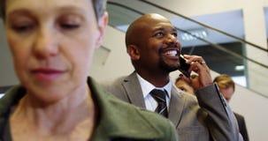 Επιχειρηματίας που μιλά στο κινητό τηλέφωνο στεμένος σε μια γραμμή απόθεμα βίντεο