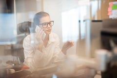 Επιχειρηματίας που μιλά στο κινητό τηλέφωνο στο γραφείο Στοκ εικόνα με δικαίωμα ελεύθερης χρήσης