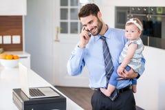 Επιχειρηματίας που μιλά στο κινητό τηλέφωνο φέρνοντας την κόρη Στοκ φωτογραφία με δικαίωμα ελεύθερης χρήσης