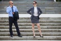 Επιχειρηματίας που μιλά στο τηλέφωνο ενώ επιχειρηματίας που στέκεται στα βήματα Στοκ Εικόνες