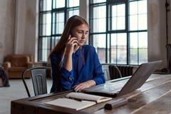 Επιχειρηματίας που μιλά στο τηλέφωνο εργαζόμενος στη συνεδρίαση lap-top στο γραφείο της στο μοντέρνο σύγχρονο γραφείο Στοκ φωτογραφία με δικαίωμα ελεύθερης χρήσης