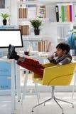Επιχειρηματίας που μιλά στο τηλέφωνο καθμένος με τα πόδια επάνω Στοκ Εικόνες