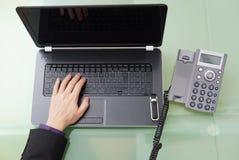 Επιχειρηματίας που μιλά στο τηλέφωνο και που εργάζεται στο lap-top στο θόριο Στοκ φωτογραφίες με δικαίωμα ελεύθερης χρήσης