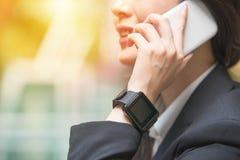 Επιχειρηματίας που μιλά στο τηλέφωνο και τον καρπό smartwatch Στοκ Εικόνες