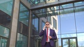 Επιχειρηματίας που μιλά στο τηλέφωνο κοντά στο σύγχρονο κτήριο φιλμ μικρού μήκους