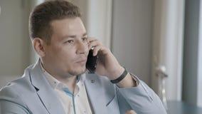 Επιχειρηματίας που μιλά στο τηλέφωνο σε ένα εστιατόριο, που εξετάζει το ρολόι του απόθεμα βίντεο