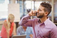 Επιχειρηματίας που μιλά στο τηλέφωνο στην αρχή Στοκ Φωτογραφίες