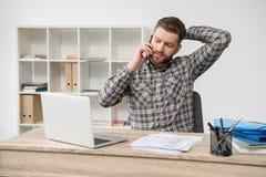 Επιχειρηματίας που μιλά στο τηλέφωνο στο σύγχρονο γραφείο Στοκ φωτογραφία με δικαίωμα ελεύθερης χρήσης