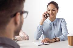 Επιχειρηματίας που μιλά στο smartphone ενώ άτομο που περιμένει στη συνεδρίαση Στοκ Εικόνες