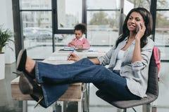 Επιχειρηματίας που μιλά στο smartphone ενώ κόρη που κάνει την εργασία Στοκ Φωτογραφίες