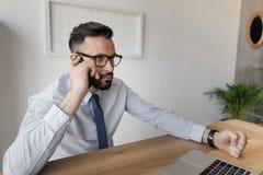 Επιχειρηματίας που μιλά στο smartphone καθμένος στον πίνακα στην αρχή Στοκ Εικόνες