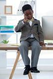 Επιχειρηματίας που μιλά στο smartphone καθμένος στο γραφείο Στοκ Φωτογραφίες