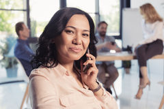 Επιχειρηματίας που μιλά στο smartphone και που εξετάζει τη κάμερα καθμένος στο γραφείο Στοκ φωτογραφίες με δικαίωμα ελεύθερης χρήσης