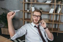Επιχειρηματίας που μιλά στο smartphone και που κρατά το αεροπλάνο εγγράφου καθμένος στον εργασιακό χώρο Στοκ Εικόνες