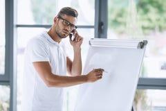 Επιχειρηματίας που μιλά στο smartphone παρουσιάζοντας στο λευκό πίνακα Στοκ Φωτογραφία