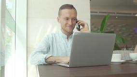 Επιχειρηματίας που μιλά στο smartphone, που λειτουργεί με το lap-top Στοκ φωτογραφία με δικαίωμα ελεύθερης χρήσης