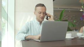 Επιχειρηματίας που μιλά στο smartphone, που λειτουργεί με το lap-top Στοκ Φωτογραφία