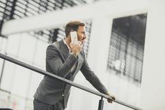 Επιχειρηματίας που μιλά στο smartphone στεμένος το εξωτερικό κοντά στο μ Στοκ εικόνες με δικαίωμα ελεύθερης χρήσης
