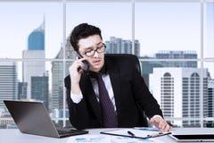 Επιχειρηματίας που μιλά τηλεφωνικώς κοντά στο παράθυρο Στοκ φωτογραφίες με δικαίωμα ελεύθερης χρήσης