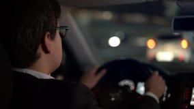 Επιχειρηματίας που οδηγεί ένα αυτοκίνητο στην πόλη νύχτας που μεταστρέφει μια πάροδο απόθεμα βίντεο