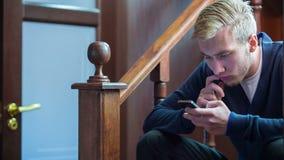 Επιχειρηματίας που παίζει το κινητό τηλέφωνο φιλμ μικρού μήκους